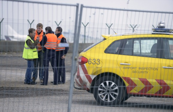 Airport security guards and officials stand near an entrance to the tarmac at Zaventem international airport near Brussels February 19, 2013. Robbers dressed as police and armed with machineguns have stolen 120 parcels of diamonds worth millions of dollars from the runway of Brussels Airport in one of the biggest heists the industry has seen.