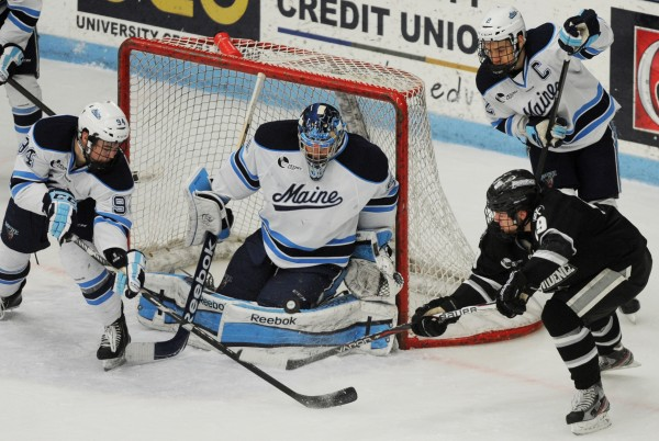 UMaine's Devin Shore helps UMaine goalie Martin Ouellette defend against Derek Army during second-period action at Orono on Friday, Feb. 1, 2013. UMaine's Mike Cornell is also in on the action.
