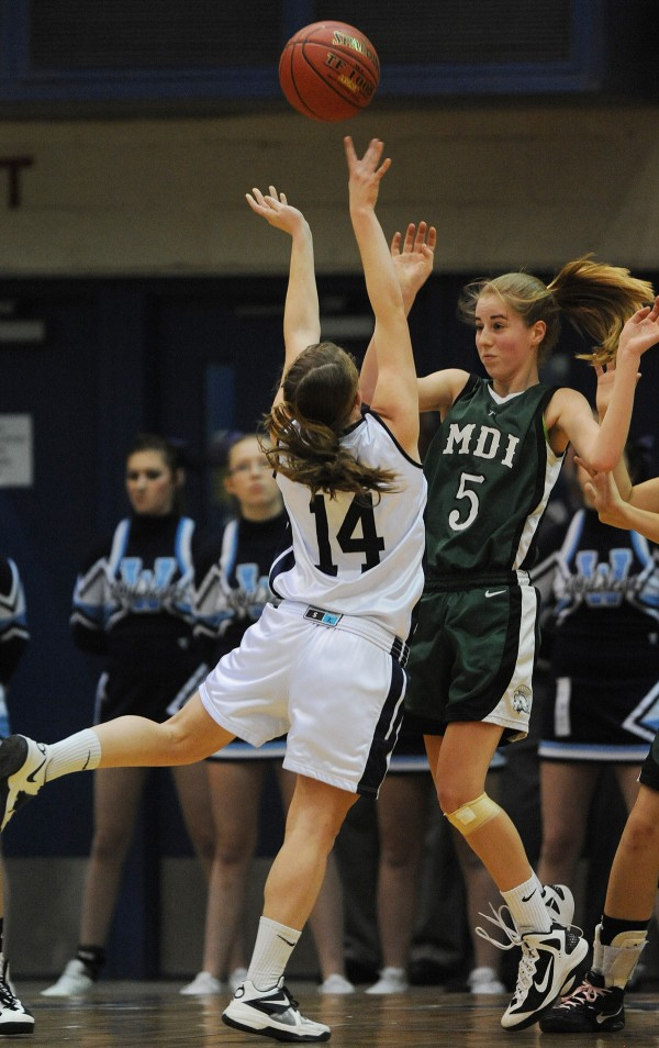 Mount Desert Island's Sarah Phelps defends as Presque Isle's Chandler Guerrette tosses up a shot during second half action on Wednesday at the Bangor Auditorium during Class B tourney action.