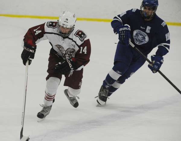Bangor's Alec Coleman-Pray reels in the puck while being chased by Lewiston's Kyle Lemelin a during high school hockey action on Thursday at Sawyer Arena in Bangor.