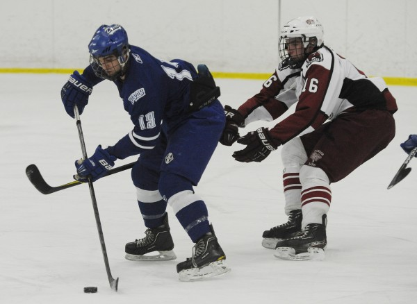 Lewiston's Kyle Lemelin and Bangor'sJustin Courtney chase down a puck during high school hockey action on Thursday at Sawyer Arena in Bangor.