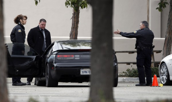 Police authorities process a black car, next to a stolen white car (right), in the parking lot of a Tustin computer store after a gunman went on a shooting spree in suburban southern California February 19, 2013. The gunman killed three people on Tuesday in an attack at a home and three carjackings, before killing himself with a shotgun as officers closed in, police said.