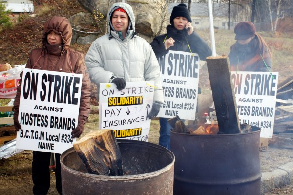 Strikers stay close to fires in barrels for warmth Friday morning Nov. 16, 2012, outside the Hostess Bakery in Biddeford.
