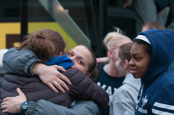 Rachele Burns, center, embraces Danielle Walczak while Chantel Charles, right, and other members of the University of Maine women's basketball team arrive back home to a crowd of family and friends on Wednesday, February 27, 2013. The bus the team was travelling on crashed Tuesday after the driver collapsed over the steering wheel, sending the bus across five lanes of traffic and into a stand of trees.