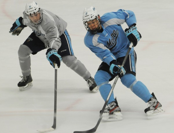 UMaine hockey players Andrew Cerretani (left) and Mike Cornell skate during practice recently at Alfond Arena.