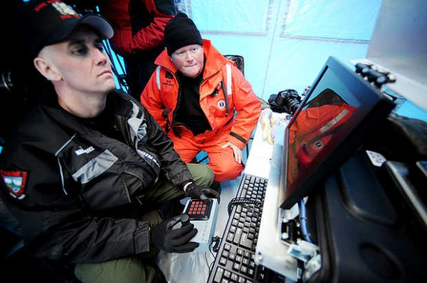 Maine Wardens Mike Joy (right) and Bruce Loring watch a screen as an underwater, remotely operated vehicle equipped with a camera searches Rangeley Lake for the bodies of Kenneth Henderson, 40, of China, Glen Henderson, 43, of Sabattus and John Spencer, 41, of Litchfield on Wednesday. The three snowmobilers have been missing since Dec. 30.