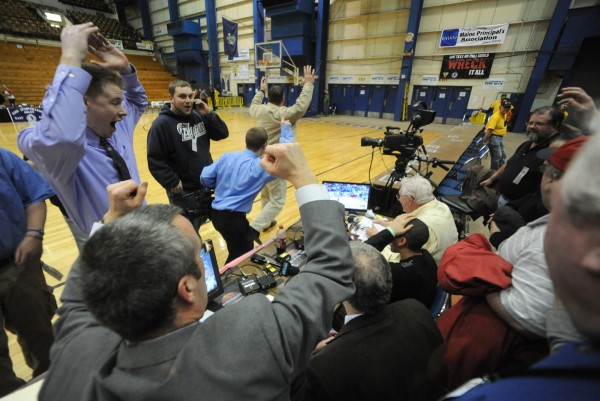 Members of the media and bystanders react to Hampden's win over Lawrence as they watch it on a small monitor along press row at the Bangor Auditorium on Friday. Hampden defeated Lawrence 40-39 with a three point shot launched from near half court by Nick Gilpin.