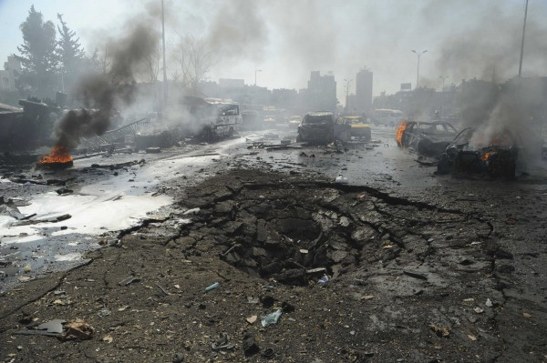 Vehicles burn near a crater on a road after an explosion at central Damascus February 21, 2013, in this handout photograph released by Syria's national news agency SANA.