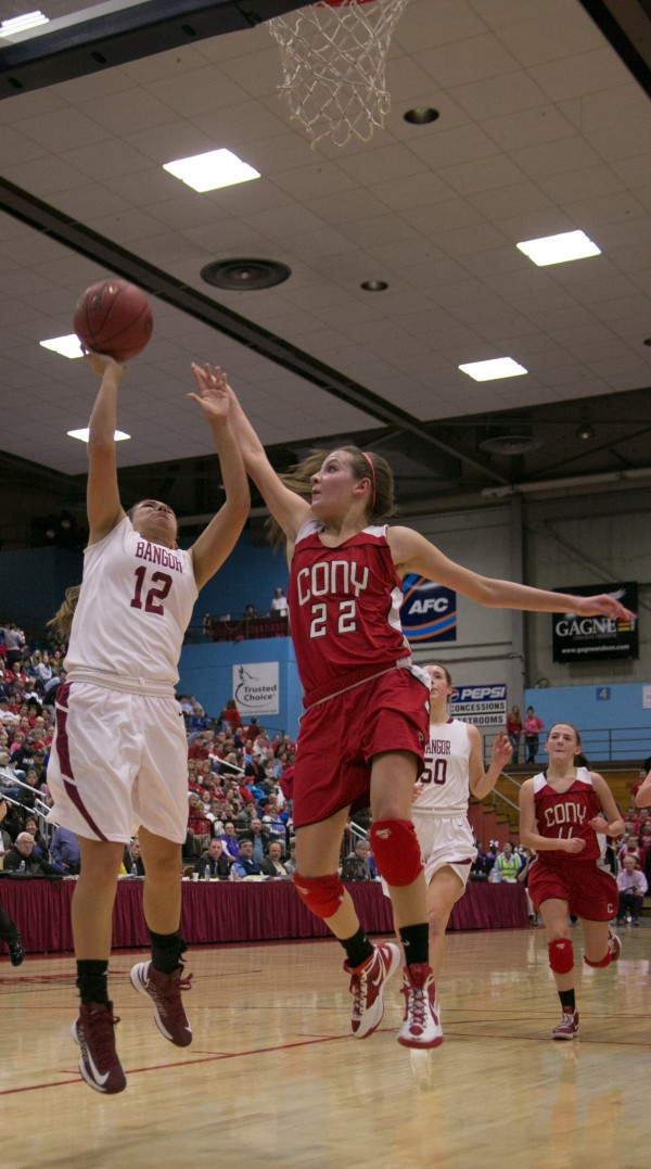 Bangor's Jordan Seekins (left) shoots a layup against Cony's Hayley Quirion (right) at the Augusta Civic Center on Friday, Feb. 22, 2013.