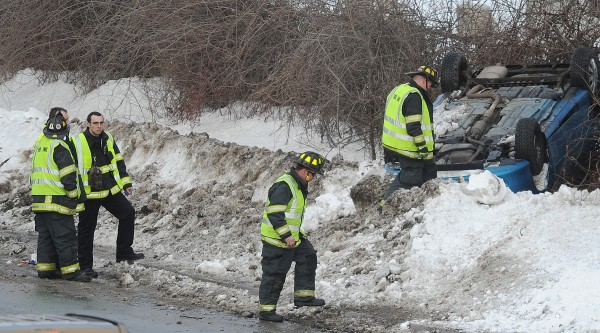 Bangor Fire Department personnel inspect a rollover over along I-95 north bound near the Kenduskeag Stream on Tuesday, Feb. 12, 2013. One person was taken to a local hospital, but police on scene said her injuries were not life threatening.