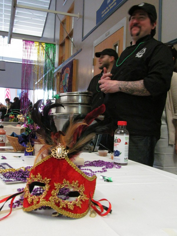 Christopher Milligan, right, and Craig Howard of the Great Lost Bear restaurant in Portland stand ready to serve up tastes of their all-local seafood gumbo while a thematic Mardi Gras-style mask guards their beads in the foreground on Feb. 12, 2013. The Great Lost Bear was one of several eateries participating in the Cajun Cooking Challenge at the University of Southern Maine in recognition of Fat Tuesday.
