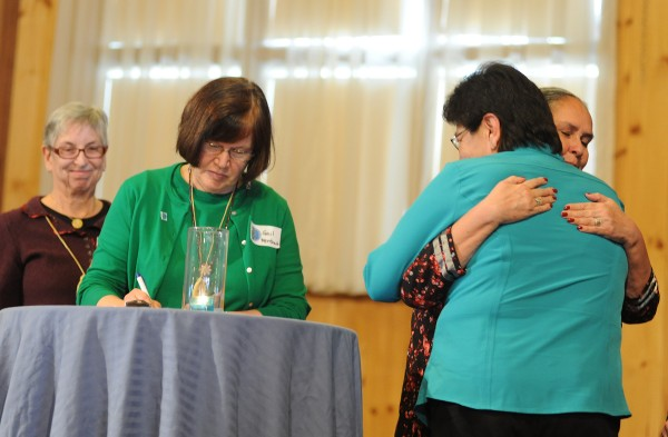 The five commissioners of the Maine Wabanaki-State Child Welfare Truth and Reconciliation Commission sign in on the commission after taking the oath Tuesday morning at the Morgan Hill Event Center in Hermon. Commissioner Sandra White Hawk (far right) hugs Molly Newell, head of social services for Passamaquoddy Tribe at Pleasant Point, after signing in on the oath. Commissioner Gail Werrbach signs in on the oath as Carol Wishcamper (far left) waits.