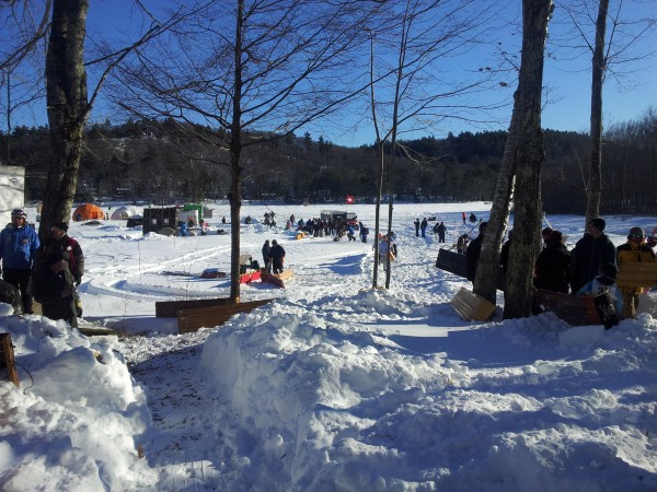 Spectators and competitors gather on Hosmer Pond to watch the US National Toboggan Championship on Feb. 10, 2013 at Camden Snow Bowl. Racers leave the chute, launch onto the pond and are eventually slowed to a stop by the snow.