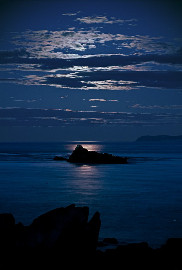 Sail Rock silhouetted by full moon and backlit clouds.