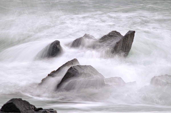 Ethereal movement of incoming surf breaking over coastal granite rock formations at Quoddy Head State Park