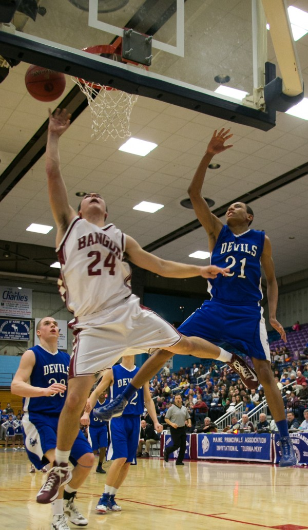 Bangor's Matt Cosgrove, left, goes up and under Lewiston defender Isaiah Harris, right, during the second half at the Augusta Civic Center on Saturday, February 16, 2013.