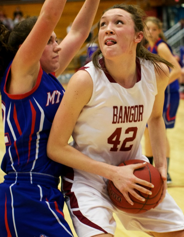 Bangor High School forward Mary Butler (right) looks to the basket Wednesday at the Class A Eastern Semifinal basketball game in Augusta.