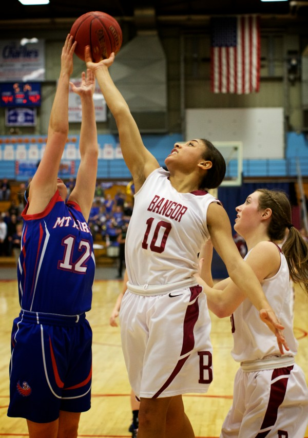 Bangor High School's Denae Johnson (right) tries for a  rebound over Mt. Ararat High School's Caitlin LaFountain Wednesday at the Class A Eastern Semifinal basketball game in Augusta.