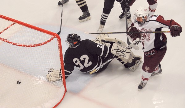 Bangor High School's Nick Graham (right) puts the puck in the net past Maranacook/Hall-Dale/Winthrop High School's goalie Tyler Plante during the second period of the game in Bangor Tuesday evening.