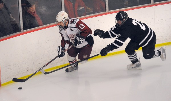 Bangor High School's Zeb Tuell (left) and Maranacook/Hall-Dale/Winthrop High School's Zach Goudbout battle for the puck during the second period of the game in Bangor Tuesday evening.