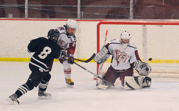 Bangor High School's goalie Rye Powell (right) cant make the save on a shot by Maranacook/Hall-Dale/Winthrop High School's Matthew Plourde (left) during the second period of the game in Bangor Tuesday evening. At center is Bangor's Sam Huston.