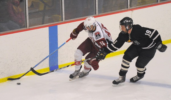 Bangor High School's Jordan Tracy (left) and Maranacook/Hall-Dale/Winthrop High School's Zach Besette battle for the puck during the first period of the game in Bangor Tuesday evening.