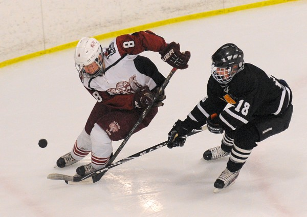 Bangor High School's Nick Graham (left) and Maranacook/Hall-Dale/Winthrop High School's Zack Phinney battle for the puck during the second period of the game in Bangor Tuesday evening.