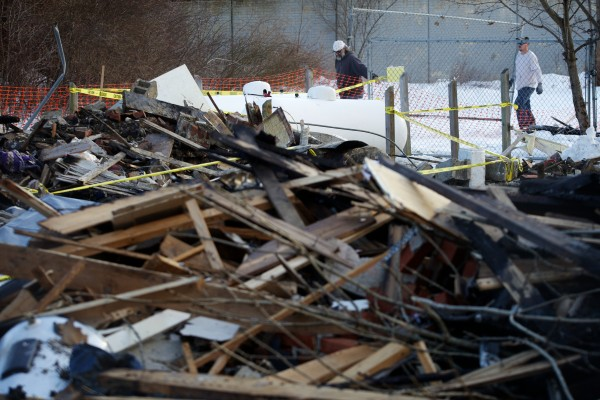 Workmen erect a fence around the remains of Bluff Road duplex in Bath Wednesday, Feb. 13, 2013, which burned after a propane leak and explosion killing neighbor Dale Ann Fussell, 64, Tuesday morning.