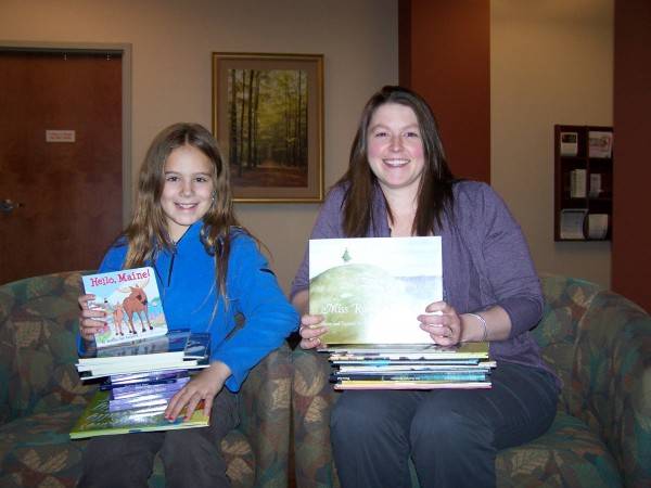 Brianna Jack (L) founder of Maine Books for Maine Kids with Krista Collins, RN, CRH ED Director and the books donated to the ED Toy Box.