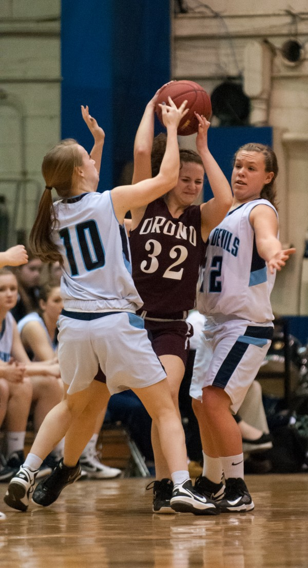 Orono's Ana Eliza Souza Cunha (center) attempts to free herself and the ball from Calais' Meaghan Cavanaugh (left) and  Olivia Smith (right) during the Eastern Maine Class C title game at the Bangor Auditorium on Saturday, February 23, 2013.