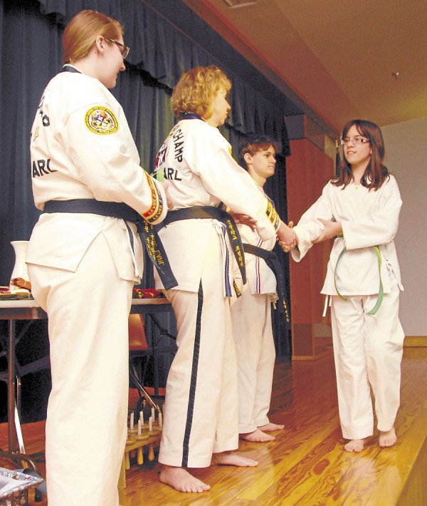 Marjorie Earl of the Hampden ATA Martial Arts School shakes hands with student Olivia Ruiz as she crosses the stage at Reeds Brook Middle School in Hampden on Thursday, Jan. 31, 2013 to receive a green belt. Assisting Earl in the ceremony are Ileft) certified instructor Rachel Earl, who holds a third degree black belt, and leadership trainee Jim Burby, who holds a second degree black belt.