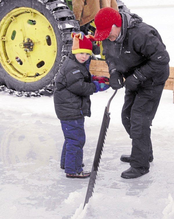 Scott Haskell of Bangor and his 6-year-old son, Jackson, push and pull on a vintage ice saw while helping cut ice blocks on Fields Pond in Orrington on Saturday, Feb. 16, 2013. The Haskells were attending the Fifth Annual Ice Harvest sponsored by the Curran Homestead Living History Farm and Museum.