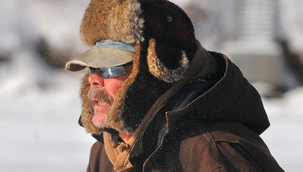 Peter Pitcher of Etna reacts as a gust of cold wind catches him while drilling a hole for ice fishing on Moosehead Lake near Rockwood in late January.