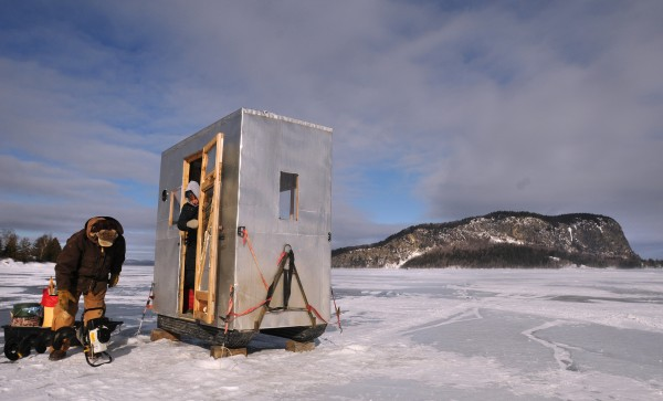Peter (left) and Janie Pitcher of Etna get their equipment organized when they arrive at their ice fishing shack on Moosehead Lake near Rockoow in late January. In the background is Mt. Kineo.