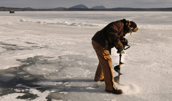 Peter Pitcher drills a hole for ice fishing on Moosehead Lake near Rockwood in late January.