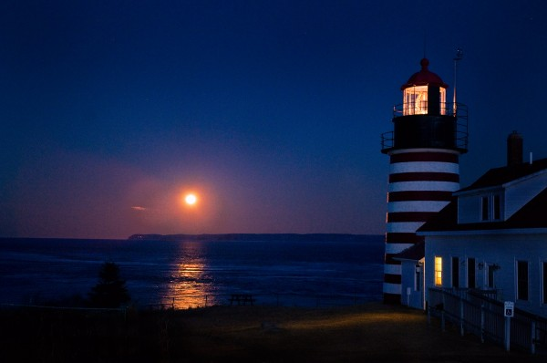 Full moon rising over Grand Manan Island, New Brunswick, Canada with West Quoddy Head Lighthouse in foreground.