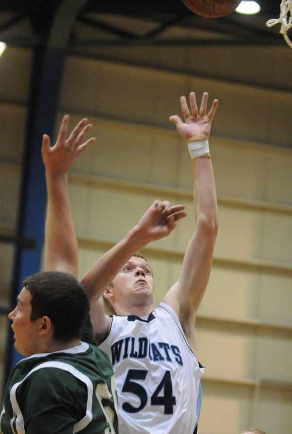 Presque Isle's Abe Philbrook tosses up a shot under pressure from MDI's Adam Gray on Wednesday at the Bangor Auditorium during Class B tourney action.
