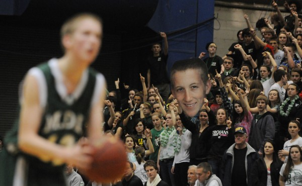 MDI's Keegan McKim shoots free throws from the line that will cement MDI's victory over Presque Isle as MDI fans in the student body hold a giant cut out of McKim on Wednesday at the Bangor Auditorium during Class B tourney action. MDI won 51-40.