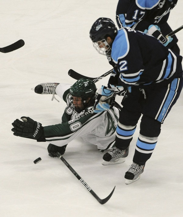 Michigan State's Dean Chelios (left) hits the puck away while fighting for possession with Maine's Kyle Solomon during the second period of the game in Orono on Oct. 16, 2009.