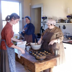 Norlands' volunteers, Anne Feith, Mary Castonguay, and Shelley Cox, bake cookies in the farmer's cottage.