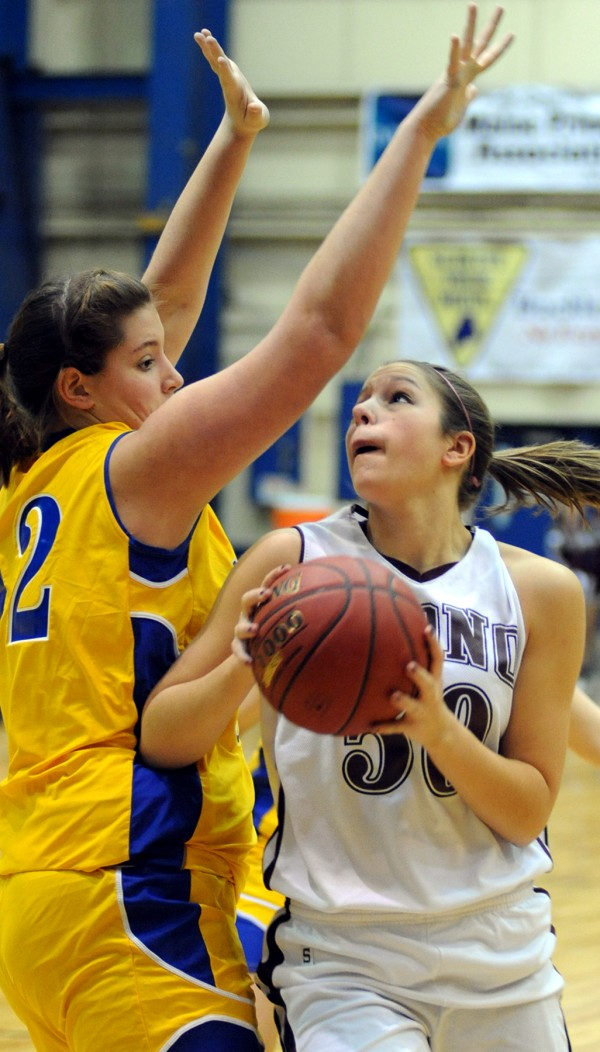 Orono's Jillian Woodward prepares to take a shot around Piscataquis defender Delani Bennett during first half action of the girls Class C quarterfinal game Tuesday morning at the Bangor Auditorium. Orono won the game 45-40 in overtime.