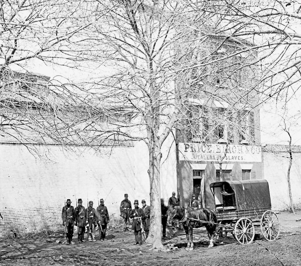 Union soldiers, of whom at least four are black infantrymen, stand outside the Price Birch & Co. in Alexandria, Va. during the Civil War. The sign on the building's exterior lists the business's name and the phrase &quotDealers in Slaves.&quot