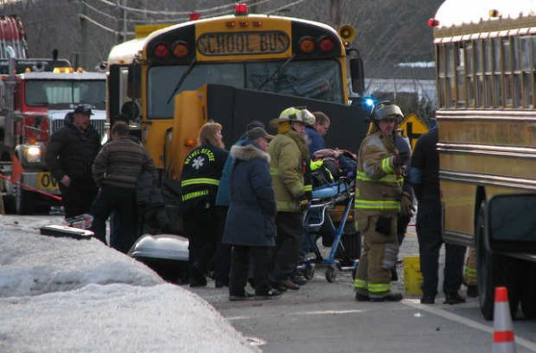 One person seriously injured in a multivehicle accident involving two schoolbuses on Friday afternoon on Route 2 in Hanover is taken from a snowbank to a waiting Med-Care Ambulance by an ambulance crew and firefighters.