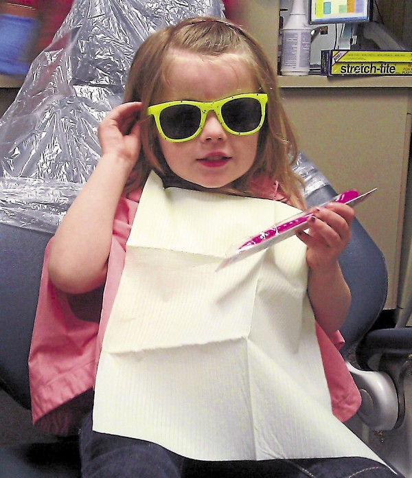 A young patient, her eyes protected by &quotover-the-top&quot sunglasses, shows off her brand new pink toothbrush after receiving dental care at Stillwater Dental Associates in Bangor.