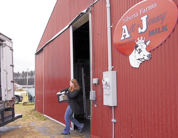 Suzanne Moreshead carries a customer's order of farm products to the delivery truck at Siberia Farms on the Newburgh Road in Hermon. Moreshead and her husband, Ed Moreshead, raise beef and dairy cattle on their farm. They started delivering their products to customers' homes in early December 2012.