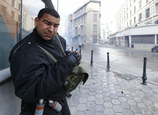 A police officer reacts after teargas was used to break up a protest in Tunis February 6, 2013. Tunisian police fired teargas to disperse protesters demonstrating in the capital outside the Interior Ministry against the killing of a prominent secular opposition politician on Wednesday, witnesses said.