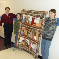 Teacher Elizabeth DeMerchant from Holbrook Middle School won the Greenville Junction Depot RR Quilt Raffle. She brought the quilt to school and showed it off with two of her Lego Club members Corbin Dunkle at left and Kaleb Fitzgerald on the right. Contributed photo