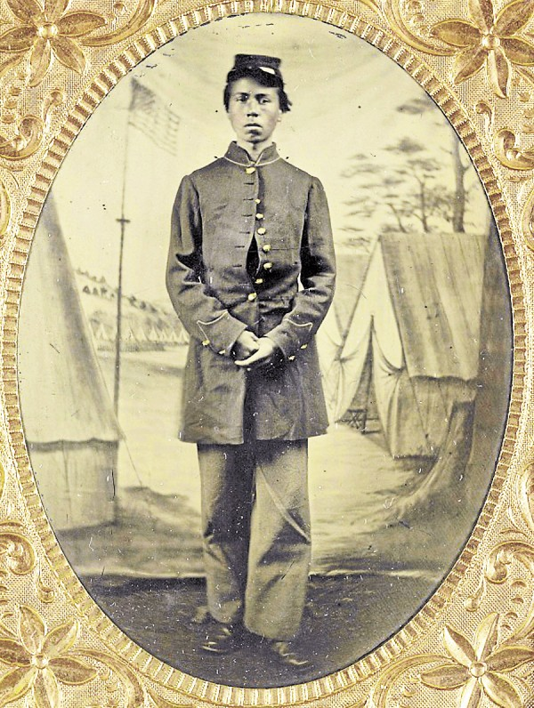 Standing before a painted backdrop of a Union army camp, an unidentified black soldier proudly wears his Federal uniform. Samuel Guess, an escaped slave who moved to Bangor after the Civil War, would have worn a similar uniform while serving with the 41st United States Colored Troops.