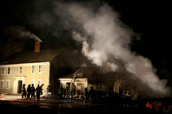Firefighters from several towns mop up a house fire in Woolwich Tuesday night on the Middle Road.