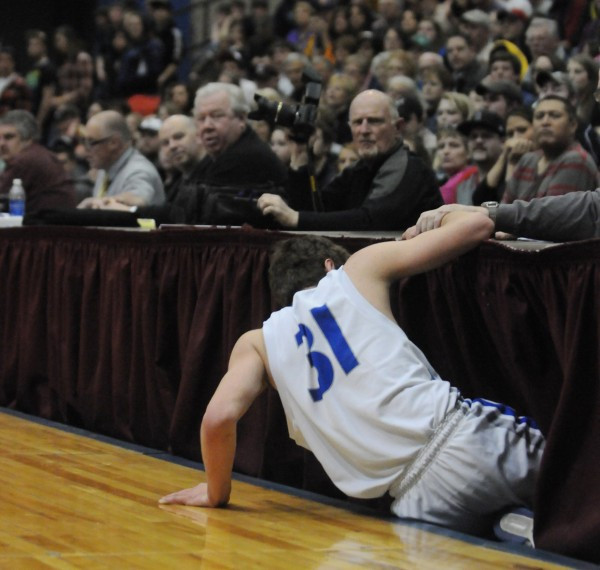 Sumner's Samuel Smith climbs out from under the press table after trying to snag a loose ball against Calais during first half actionTuesday at the Bangor Auditorium during class D tourney action.